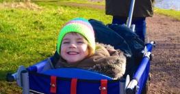 Kind sitzt lachend im Bollerwagen und lässt sich von der Mutter durch den Park ziehen.